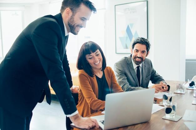 Collègues heureux rire et utilisant un ordinateur portable Photo gratuit