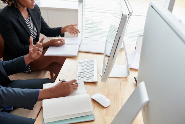 Des collègues méconnaissables regardant un écran d'ordinateur ensemble au bureau Photo gratuit
