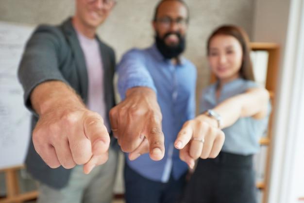 Collègues multiethniques debout dans le bureau avec les bras étendus et pointant du doigt Photo gratuit