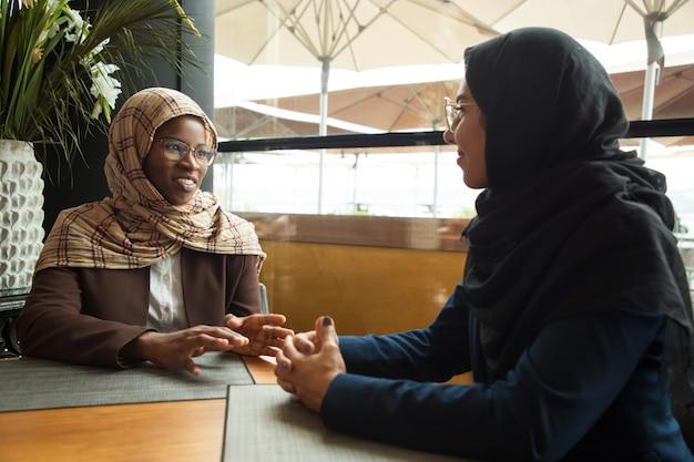 Des Collègues Musulmanes Discutant Pendant La Pause Déjeuner Photo gratuit