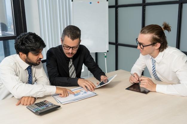 Des collègues occupés discutant de l'économie internationale à la réunion. Photo gratuit