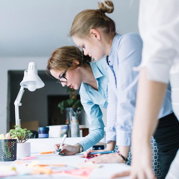 Des collègues préparant un tableau sur papier sur le bureau d'un bureau moderne Photo gratuit