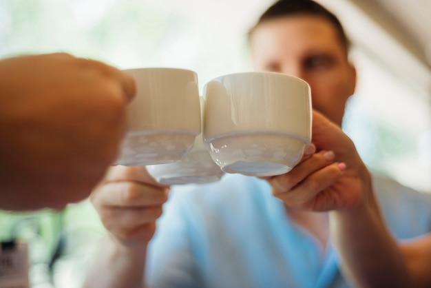 Collègues réunissant des tasses de boissons chaudes Photo gratuit