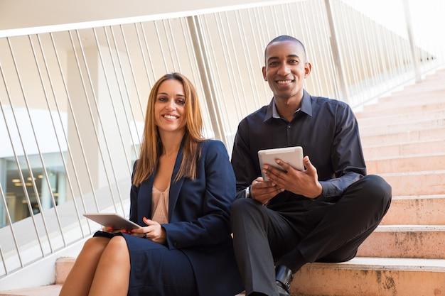 Collègues tenant des tablettes et assis dans les escaliers Photo gratuit
