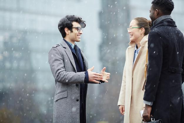 Collègues de travail discutant dans la rue enneigée Photo gratuit