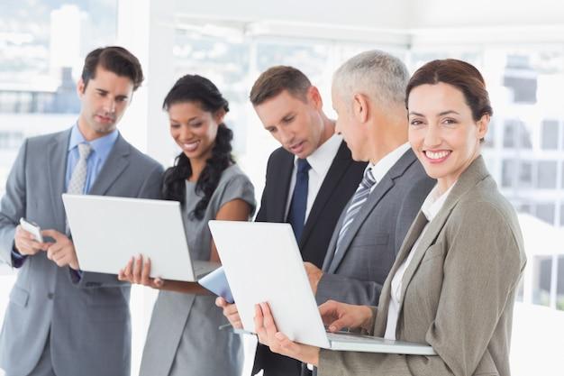 Collègues de travail montrant leurs appareils multimédia les uns aux autres Photo Premium