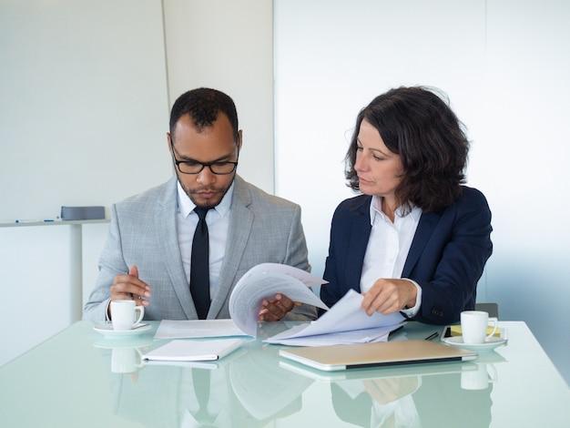 Collègues de travail vérifiant le texte de l'accord Photo gratuit