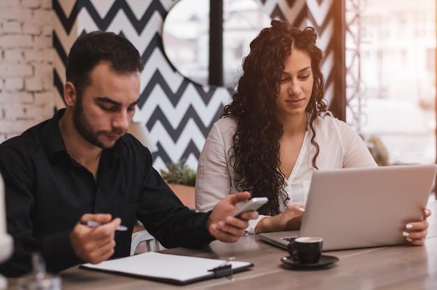 Collègues travaillant ensemble sur un ordinateur dans un café Photo Premium