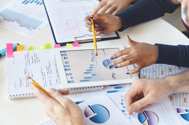 Collègues Travaillant Ensemble Sur Un Rapport Financier à L'aide D'un Gadget Moderne. Photo gratuit