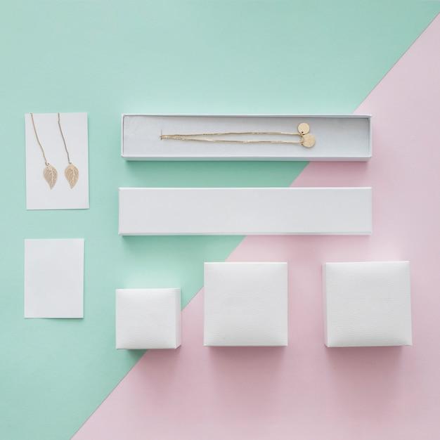 Collier en or et boucles d'oreilles avec différentes boîtes sur fond pastel Photo gratuit