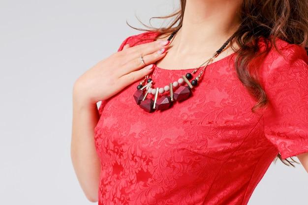 Collier original sur jeune femme en élégante robe rouge Photo Premium