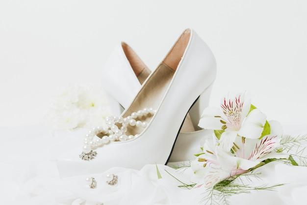 Collier de perles; des boucles d'oreilles; mariage talons hauts et bouquet de fleurs sur l'écharpe Photo gratuit