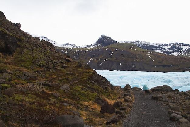 Collines Couvertes De Neige Et D'herbe Entourées D'un Lac Gelé Dans Le Parc National De Vatnajokull Photo gratuit