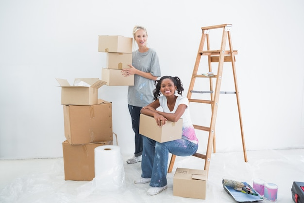 Colocataires souriants portant des boîtes de déménagement en carton Photo Premium