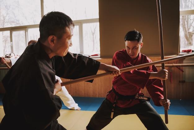 Combattants d'arts martiaux de kung-fu combattant avec des bâtons Photo Premium
