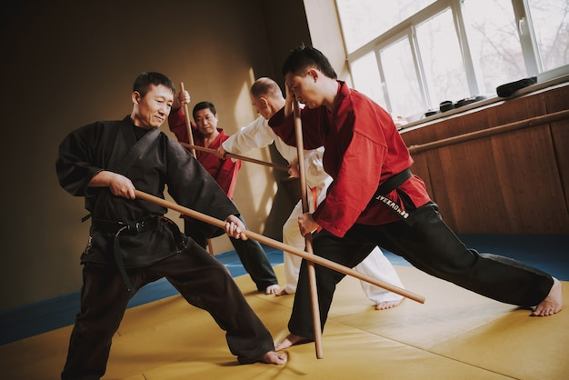 Combattants d'arts martiaux se battant avec des bâtons. Photo Premium