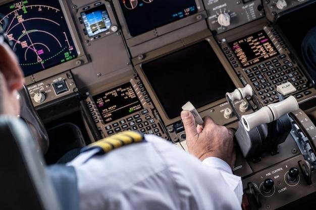 Le commandant de bord commandant l'avion dans le poste de pilotage tirant sur le levier de frein à main pour ralentir sa vitesse. Photo Premium