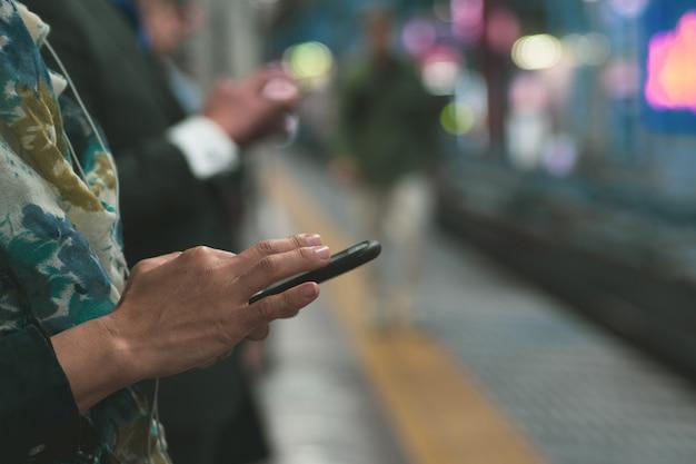 La communication. personnes utilisant un téléphone portable sur une plateforme Photo Premium