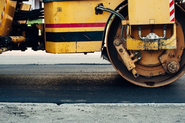 Un compacteur d'asphalte jaune aligne la route. pose de nouvel asphalte. Photo Premium