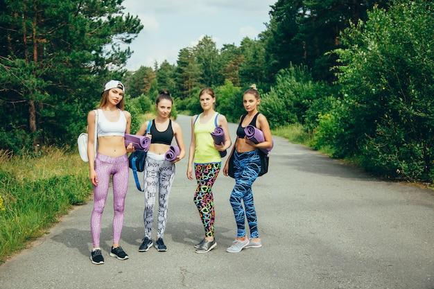 La compagnie de jeunes amies attrayantes avec des équipements sportifs qui s'entraînent dans le parc. Photo Premium
