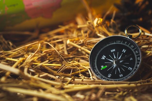 Compas avec des cartes en papier et des fleurs de pin posées sur la paille de blé sèche au soleil du matin Photo Premium