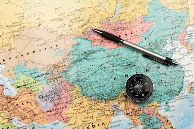 Compas magnétique et un stylo sur la carte. Photo Premium