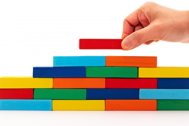 Complétez le concept de solutions d'affaires, un morceau de puzzle en bois posé sur une pile en bois Photo Premium