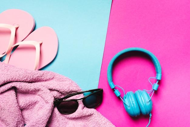 Composition d'accessoires de plage et d'écouteurs sur fond multicolore Photo gratuit