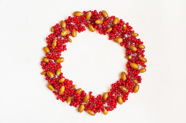Composition d'automne avec des baies rouges et des glands. couronne faite de baies de viorne. Photo Premium