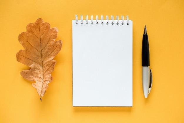 Composition d'automne. bloc-notes vide blanc, feuille de chêne orange séchée et stylo sur jaune Photo Premium