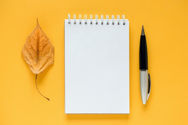 Composition d'automne. bloc-notes vide blanc, feuille d'orange séchée et stylo sur jaune. Photo Premium