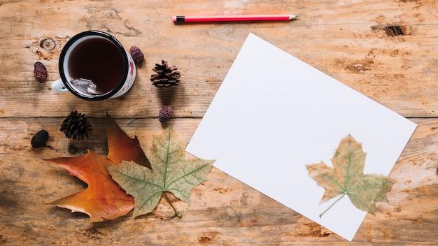 Composition de l'automne avec des feuilles et du thé sur fond en bois Photo gratuit