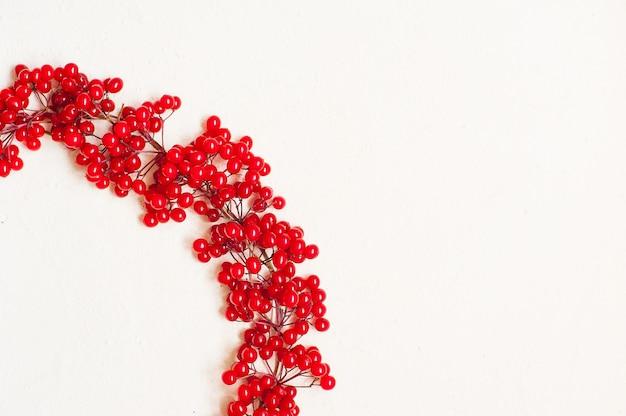 Composition d'automne avec des fruits rouges. couronne faite de baies de viorne. Photo Premium