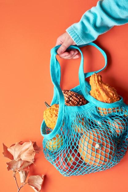 Composition D'automne: Sac à Cordes Turquoise Avec Citrouilles Et Main Féminine En Pull Bleu Sur Papier Orange Photo Premium