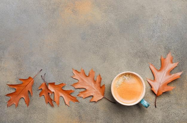 Composition d'automne avec une tasse de café et de feuilles d'automne sur fond de pierre ou de béton plat lay top view copy space Photo Premium