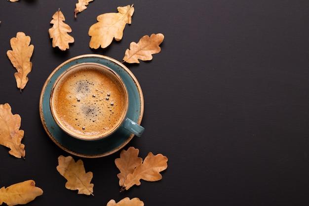 Composition d'automne. tasse de café et de feuilles sèches sur fond noir. Photo Premium