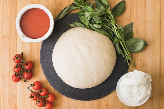 Composition avec basilic bio frais vert et ingrédients pour pizza sur fond en bois Photo gratuit