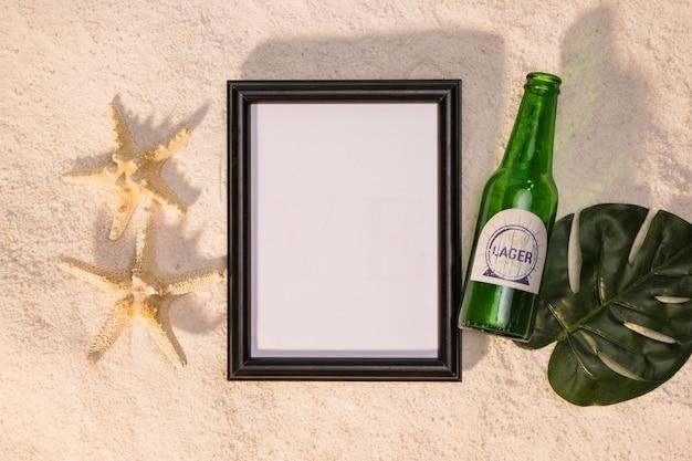 Composition de bouteille d'étoile de mer tableau blanc de boisson et feuille de monstera sur le sable Photo gratuit