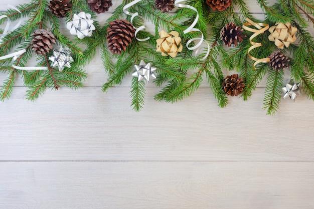 Composition de branches de sapin, de rubans d'or et d'argent et de cônes sur un fond en bois clair. Photo Premium