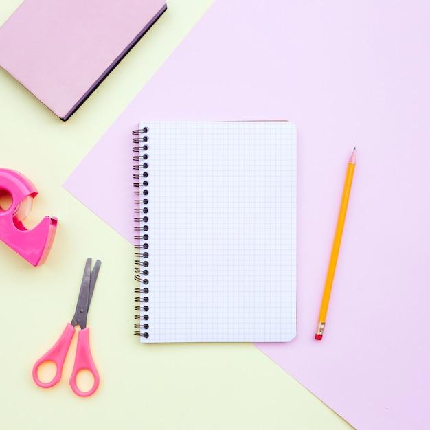 Composition de bureau avec carnet, crayon, ciseaux et livre sur le rose et le jaune Photo gratuit