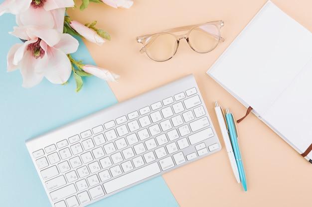 Composition de cahier, clavier, lunettes, fleurs et stylos Photo gratuit