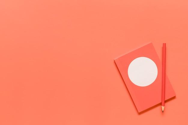 Composition de cahier rose et crayon rouge Photo gratuit