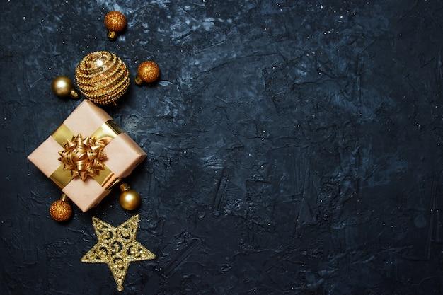 Composition De Carte De Voeux De Noël. Cadeau Avec Décoration De Noël Dorée Sur Fond Bleu Foncé. Photo Premium