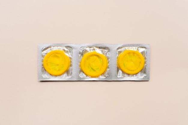 Composition Colorée Avec Des Préservatifs Jaunes Sur Une Surface Beige. Sexe Sans Risque Et Concept Contraceptif Photo Premium