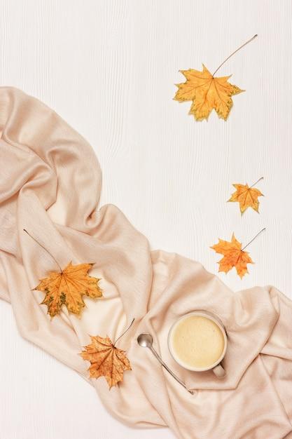 Composition Confortable D'automne Avec Des Feuilles Séchées D'érable Et Une écharpe Beige Pastel, Tasse De Café Sur Fond De Bois Blanc. Photo Premium