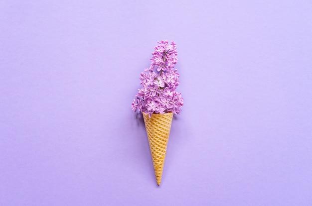 Composition de cornet de crème glacée à fleurs lilas violettes. lay plat. vue de dessus. concept d'été créatif Photo Premium