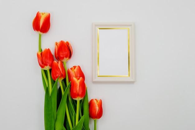 Composition créative avec la maquette du cadre photo, tulipes rouges sur fond abstrait. Photo Premium