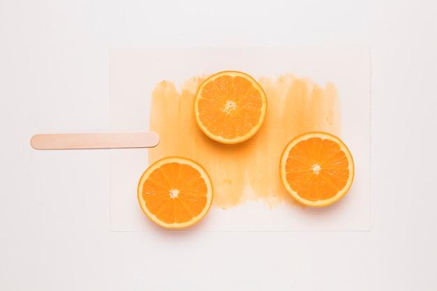Composition créative de popsicle d'orange tranchée sur un bâton Photo gratuit
