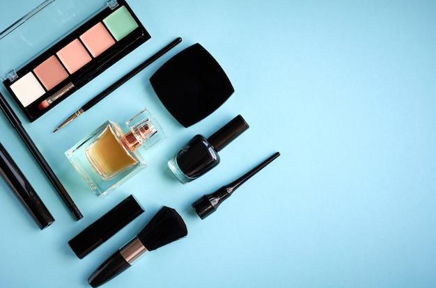 Composition de différents produits de maquillage sur fond bleu Photo Premium