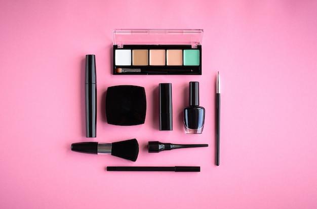 Composition de différents produits de maquillage sur fond rose Photo Premium